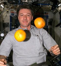 Astronaut C. Michael Foale auf der ISS. Vor ihm schweben zwei Grapefruits