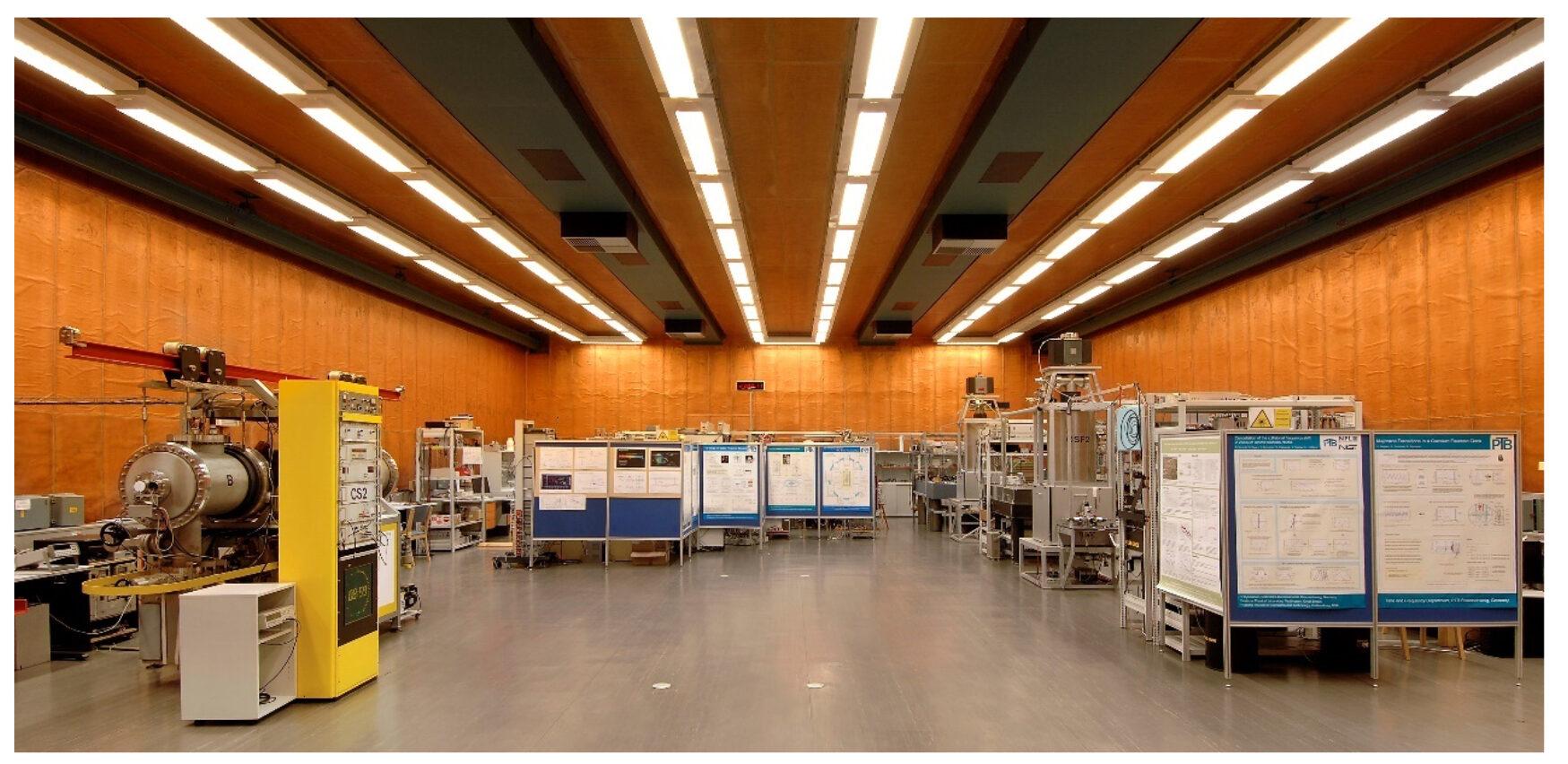 Eine große mit Deckenlampen beleuchtete Halle mit Atomuhren und wissenschaftlichen Postern